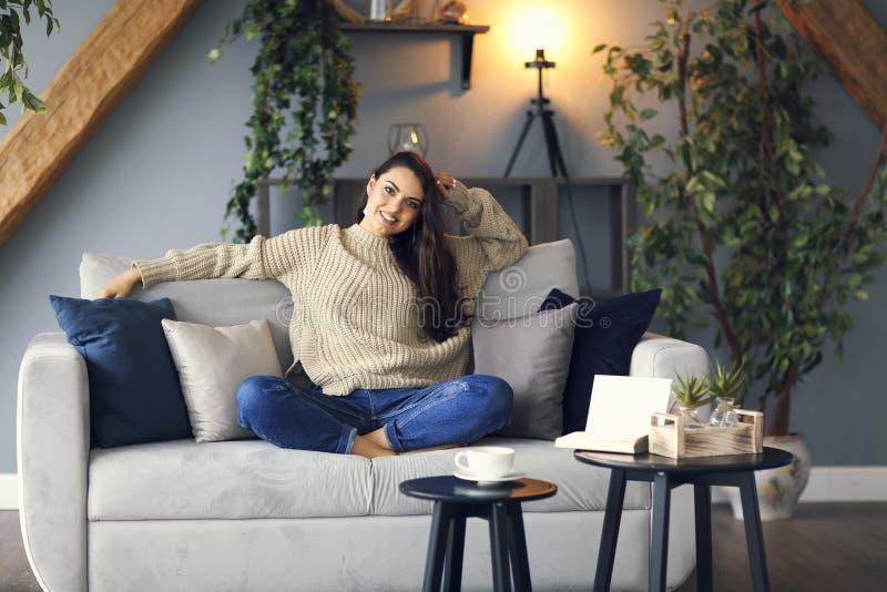 Młoda szczęśliwa brunetki kobieta z książkowym jest ubranym pulowerem obrazy stock