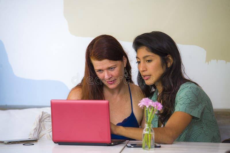 Młoda szczęśliwa caucasian kobieta i piękna latynoska dziewczyna pracuje przy biurową kawiarnią z laptopem dyskutuje jako cyfrowy fotografia royalty free