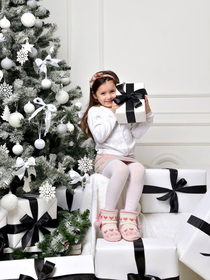 Młoda szczęśliwa dziewczyna siedzi blisko dekorującej choinki z pres obraz royalty free