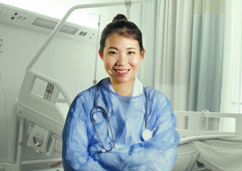 Młoda szczęśliwa i atrakcyjna Azjatycka Chińskiej medycyny lekarki kobieta w błękicie szoruje ono uśmiecha się rozochocony przy s obraz stock