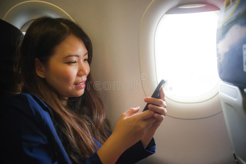 Młoda szczęśliwa i piękna Azjatycka Chińska kobieta podróżuje dla biznesu wśrodku samolotowego kabinowego ono uśmiecha się rozoch obrazy stock