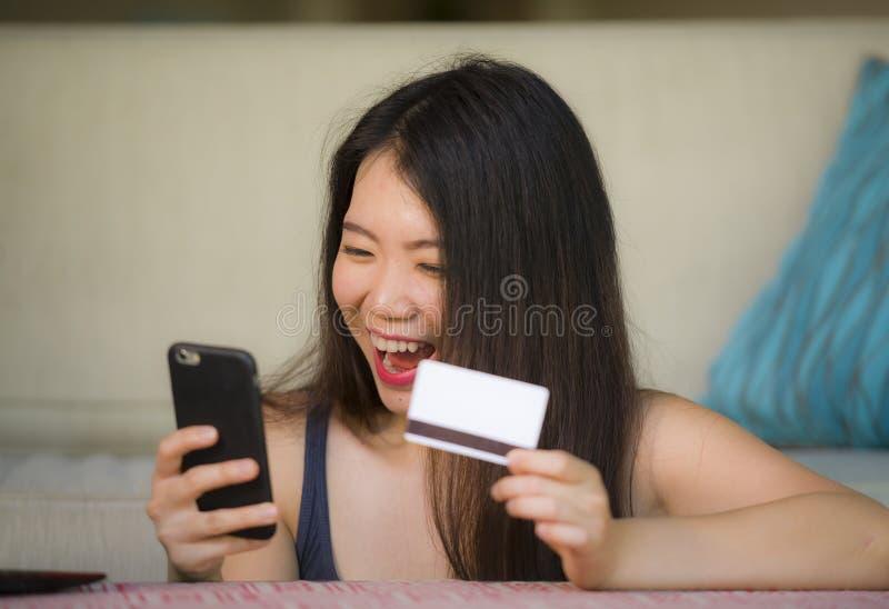 Młoda szczęśliwa i piękna Azjatycka Chińska kobiety mienia karta kredytowa używać telefon komórkowego dla internet bankowość i on zdjęcia royalty free