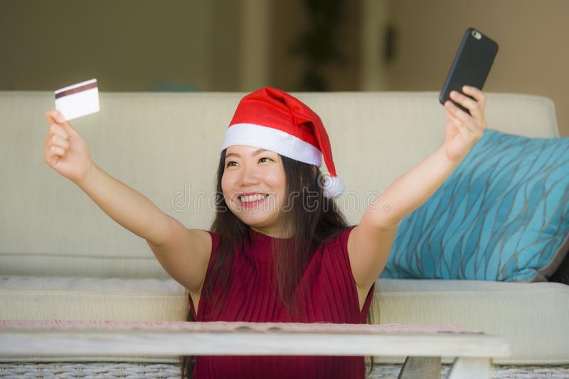 Młoda szczęśliwa i piękna Azjatycka Koreańska kobieta w Święty Mikołaj mienia kapeluszowej karcie kredytowej używać telefon komór fotografia royalty free