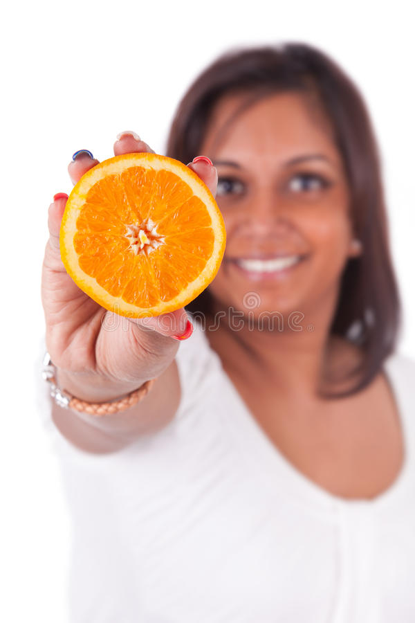 Młoda szczęśliwa indyjska kobieta trzyma pomarańczowego plasterek fotografia royalty free
