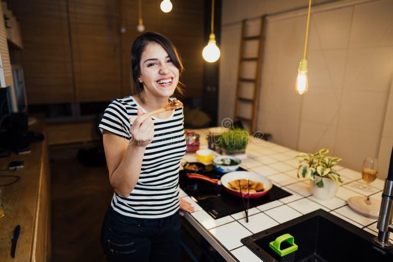 Młoda szczęśliwa kobieta gotuje zdrowego posiłek w domowej kuchni Robić gościowi restauracji stoi bezczynnie indukcji hob na kuch obrazy stock