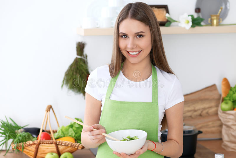 Młoda szczęśliwa kobieta jest gotująca świeżej sałatki w kuchni lub jedząca Jedzenie i zdrowia pojęcie obraz royalty free