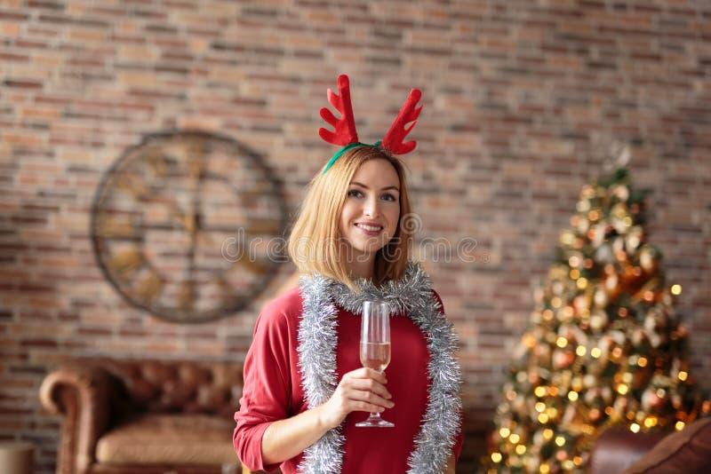 Młoda szczęśliwa kobieta jest ubranym czerwieni suknię z poroże kapitałki jeleniego mienia szampańskim szkłem podczas gdy ono uśm fotografia royalty free