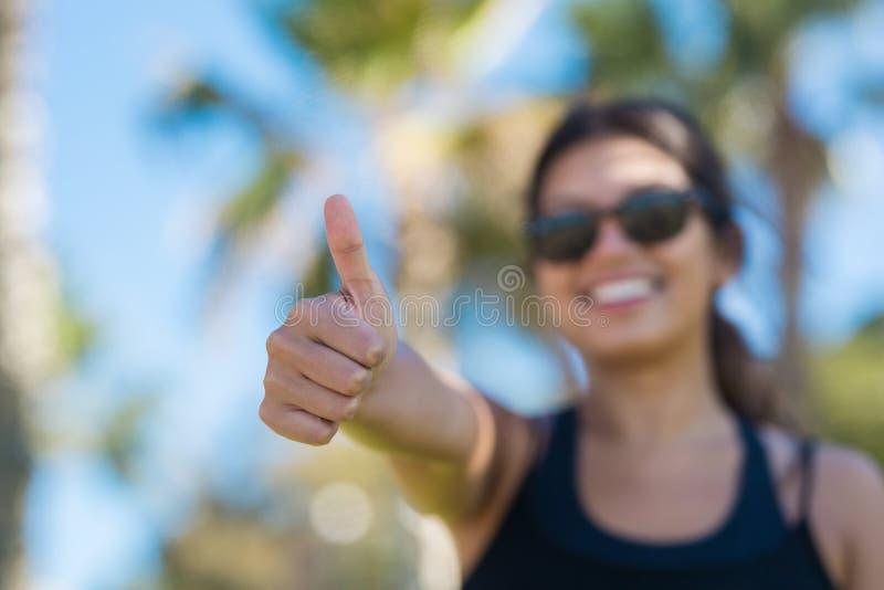 Młoda szczęśliwa kobieta pokazuje kciuk up fotografia stock