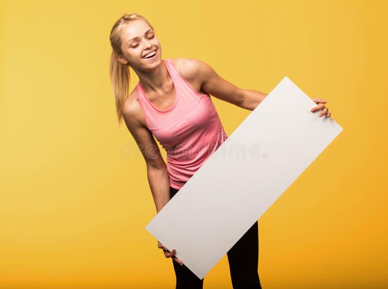 Młoda szczęśliwa kobieta pokazuje prezentację, wskazuje na plakacie fotografia royalty free