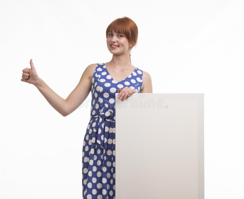 Młoda szczęśliwa kobieta pokazuje prezentację, wskazuje na plakacie obrazy stock