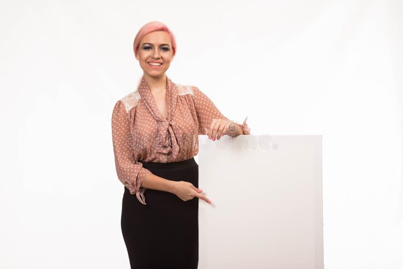 Młoda szczęśliwa kobieta pokazuje prezentację, wskazuje na plakacie obraz stock
