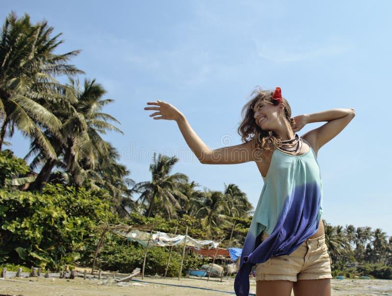Młoda szczęśliwa kobieta przy plażą wśród palm ono uśmiecha się fotografia stock