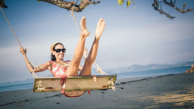 Młoda szczęśliwa kobieta relaksuje przy huśtawką przy tropikalną ocean plażą fotografia stock