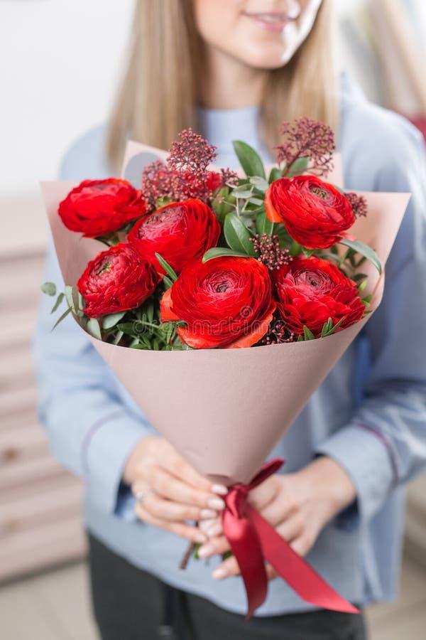 Młoda szczęśliwa kobieta trzyma piękną wiązkę czerwoni jaskiery lub Ranunculus w ona ręki Teraźniejszość dla uśmiech dziewczyny obrazy stock