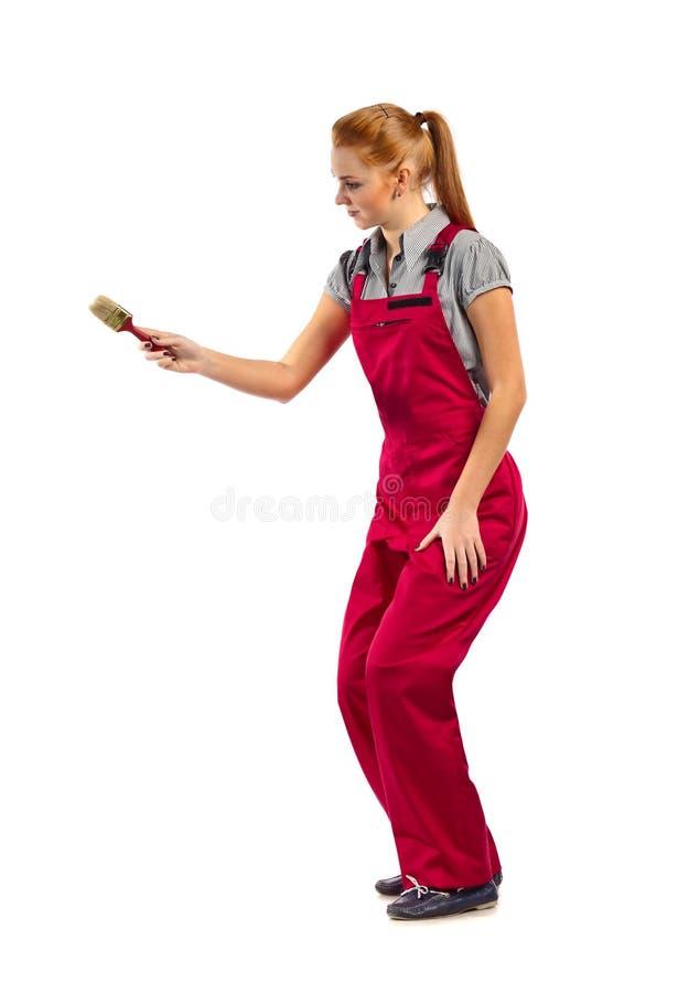 Młoda szczęśliwa kobieta w czerwonym kombinezonie z farby muśnięciem obrazy stock