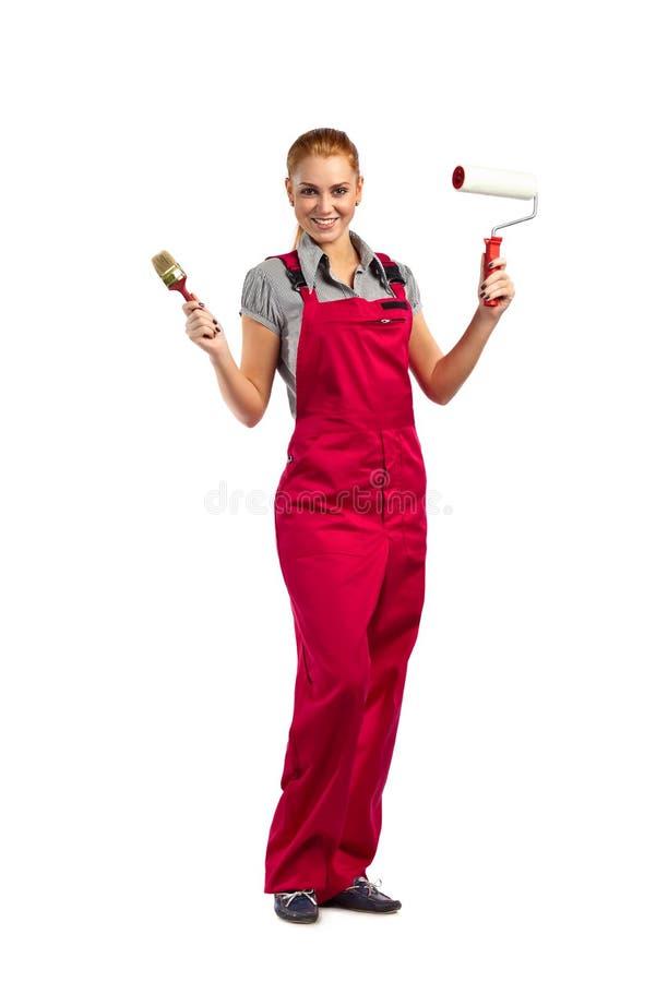 Młoda szczęśliwa kobieta w czerwonym kombinezonie z obrazów narzędziami fotografia stock
