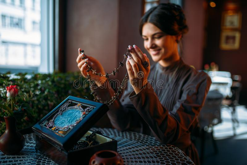 Młoda szczęśliwa kobieta w kawiarni z szkatułą i biżuterią obraz royalty free