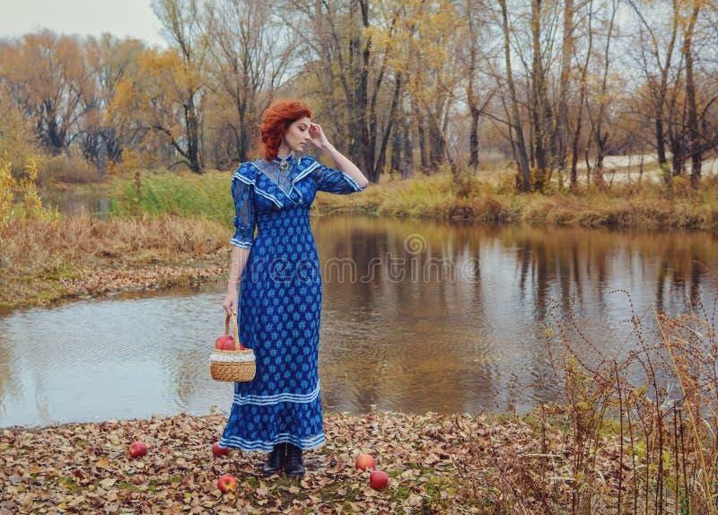 Młoda szczęśliwa kobieta w parku blisko rzeki w jesień sezonie zdjęcia stock