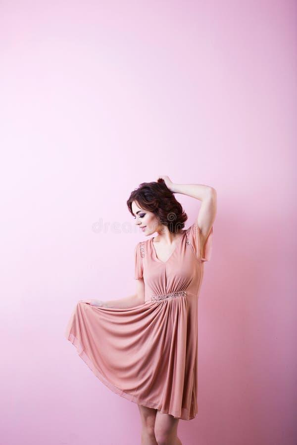 Młoda szczęśliwa kobieta w różowej sukni zdjęcie stock