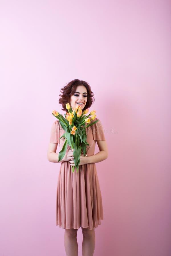 Młoda szczęśliwa kobieta z bukietem kwiatów tulipany na menchii fotografia royalty free