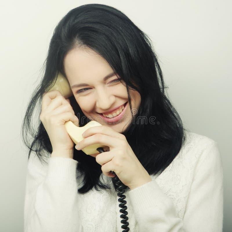 Młoda szczęśliwa kobieta z rocznika telefonem zdjęcia stock
