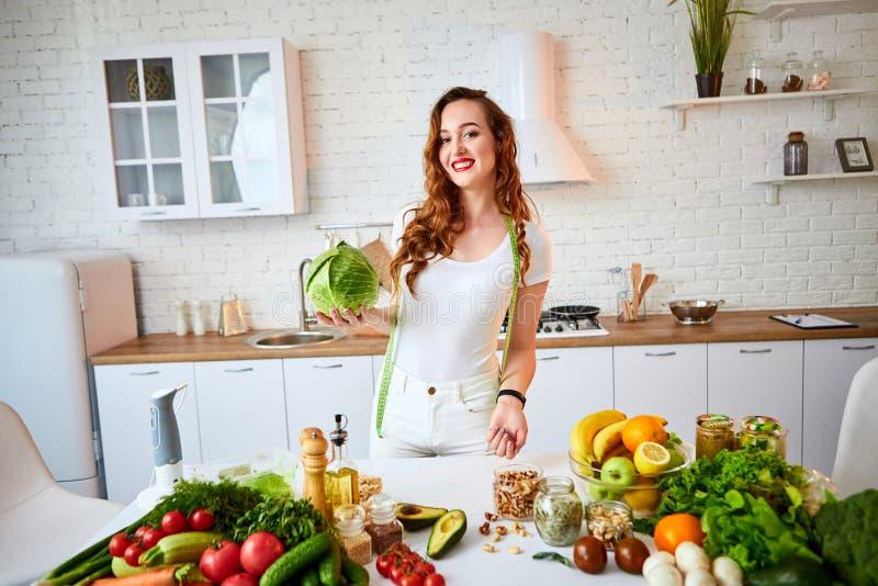 Młoda szczęśliwa kobiety mienia kapusta w pięknej kuchni z zielonymi świeżymi składnikami indoors Zdrowy jedzenie i Dieting poj?c zdjęcie royalty free