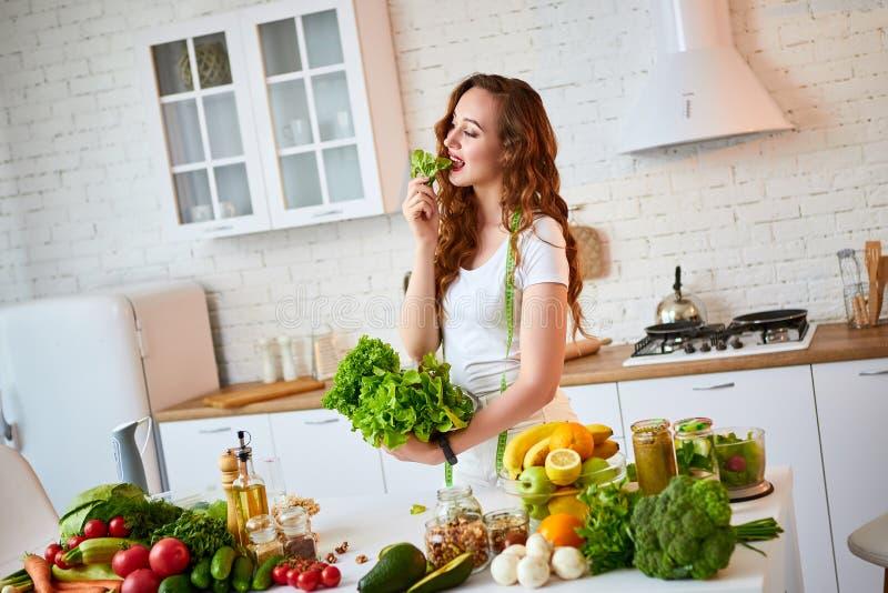 Młoda szczęśliwa kobiety mienia sałata opuszcza dla robić sałatki indoors w pięknej kuchni z zielonymi świeżymi składnikami Zdrow zdjęcia stock