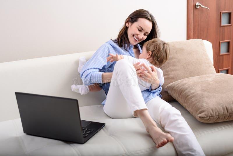 Młoda szczęśliwa mama bawiąca się z dzieckiem na kanapie, urlop macierzyński, zdalna praca na laptopie fotografia royalty free