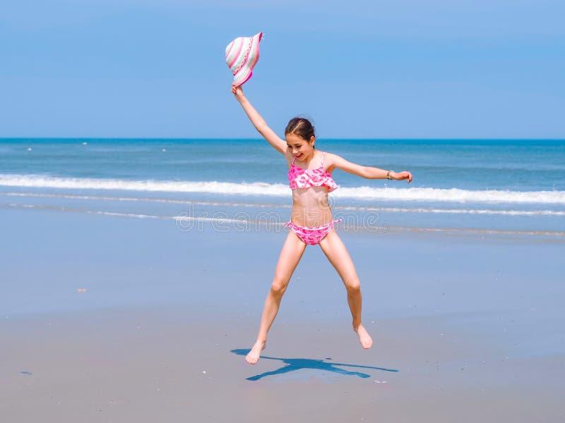 Młoda szczęśliwa nastoletnia dziewczyna ma zabawę na tropikalnej plaży, doskakiwanie w w powietrze na dennym wybrzeżu i fotografia stock