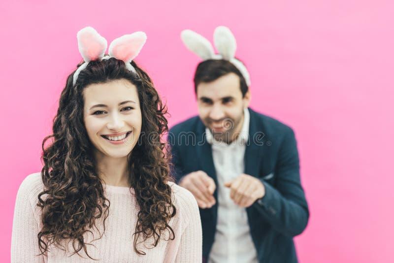 Młoda szczęśliwa para na różowym tle Na głowie są królika ucho Młoda dziewczyna stojaki na rozmytym tle zdjęcia stock
