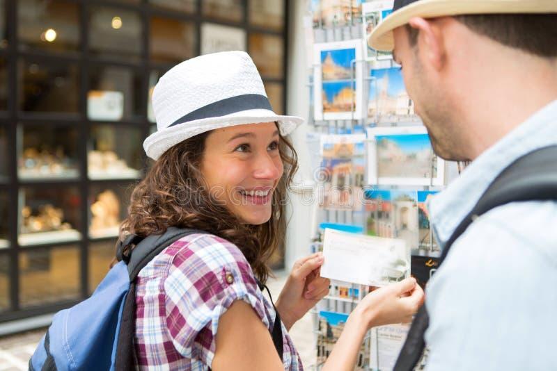 Młoda szczęśliwa para wybiera pocztówki podczas wakacji obrazy royalty free