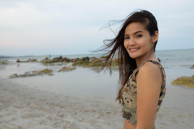 Młoda szczęśliwa piękna Azjatycka kobieta ono uśmiecha się przy jawną plażą fotografia royalty free