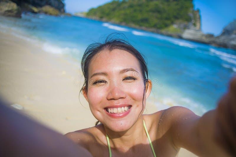 młoda szczęśliwa, piękna Azjatycka turystyczna kobieta w bikini bierze jaźń portreta selfie fotografię przy raj plażą i obrazy stock