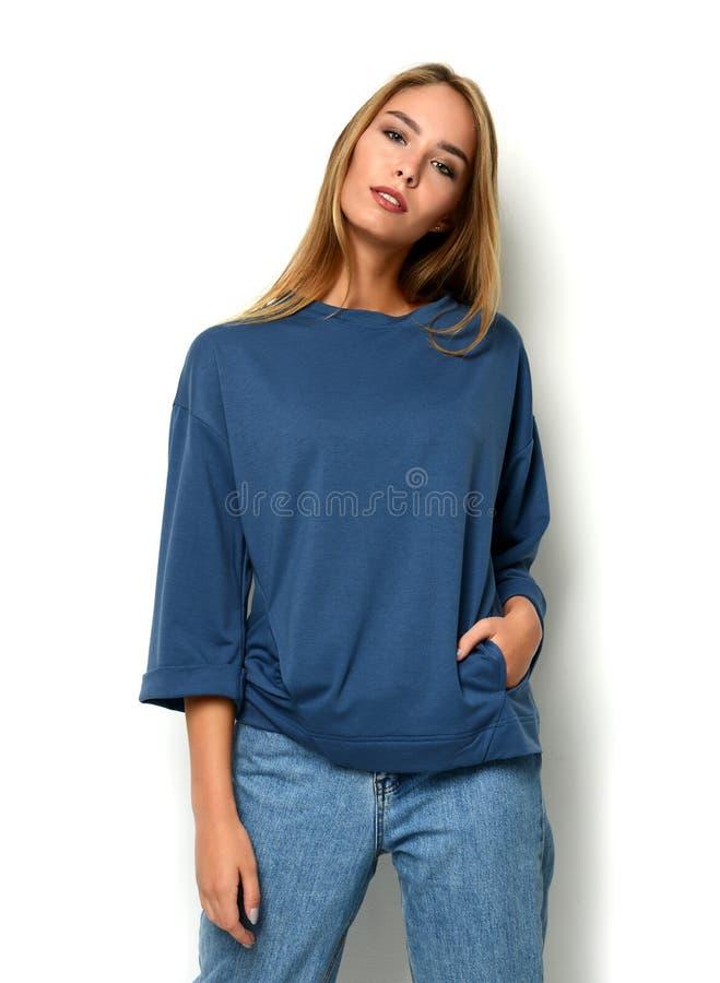 Młoda szczęśliwa piękna kobieta pozuje w nowych moda niebieskich dżinsach, pulowerze i obraz stock