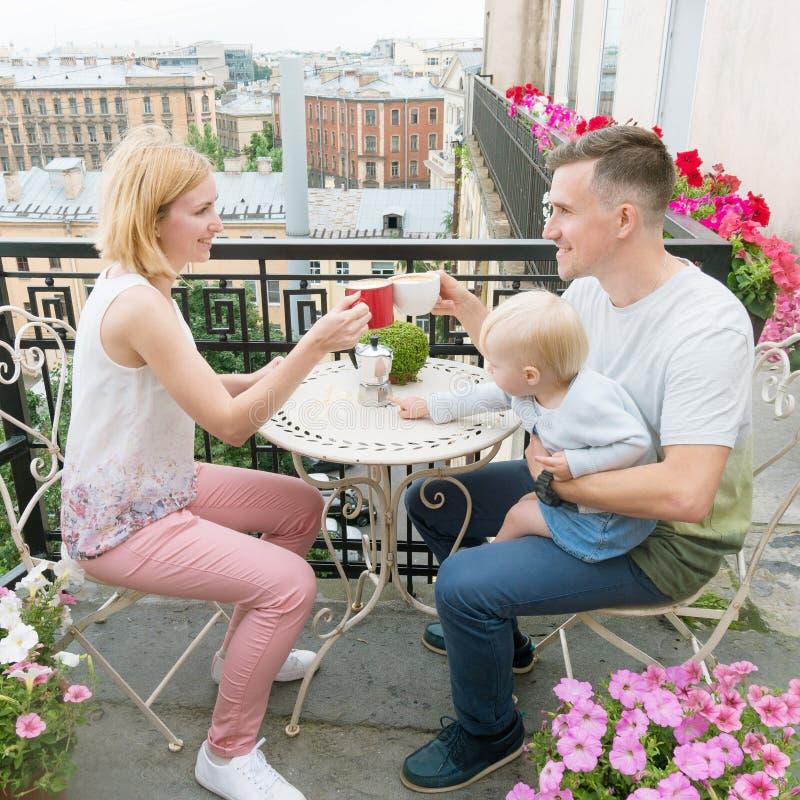 Młoda szczęśliwa rodzina pije poranną kawę obraz stock