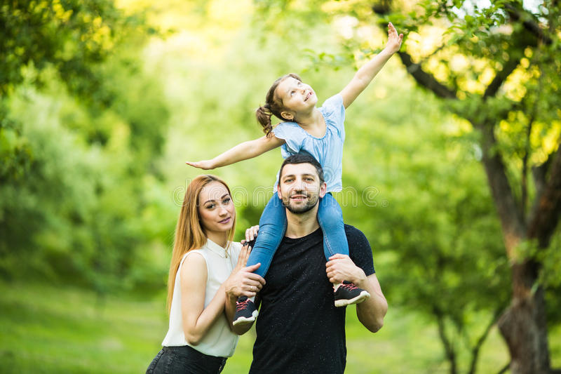 Młoda szczęśliwa rodzina trzy ma zabawę wpólnie plenerową Dosyć mała córka na jej ojcu z powrotem Rodzinna zabawa outside fotografia stock