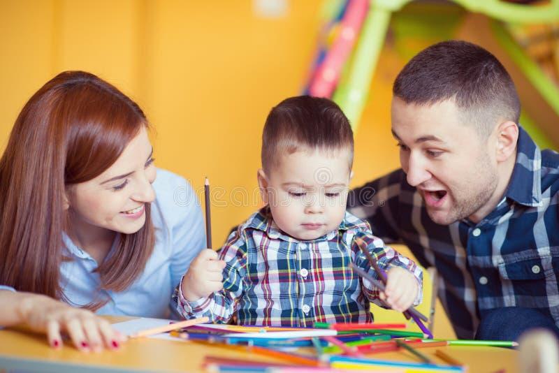 Młoda szczęśliwa rodzina z berbeć chłopiec bawić się wpólnie w domu obraz royalty free
