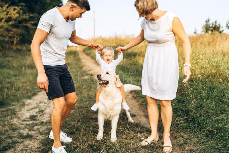 Młoda szczęśliwa rodzina z psem zabawę plenerową zdjęcia stock