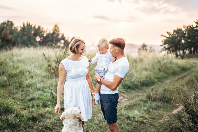 Młoda szczęśliwa rodzina z psem zabawę plenerową obraz royalty free