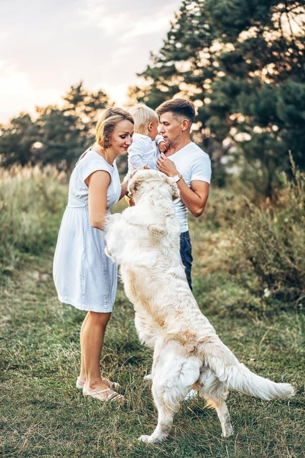 Młoda szczęśliwa rodzina z psem zabawę plenerową fotografia stock