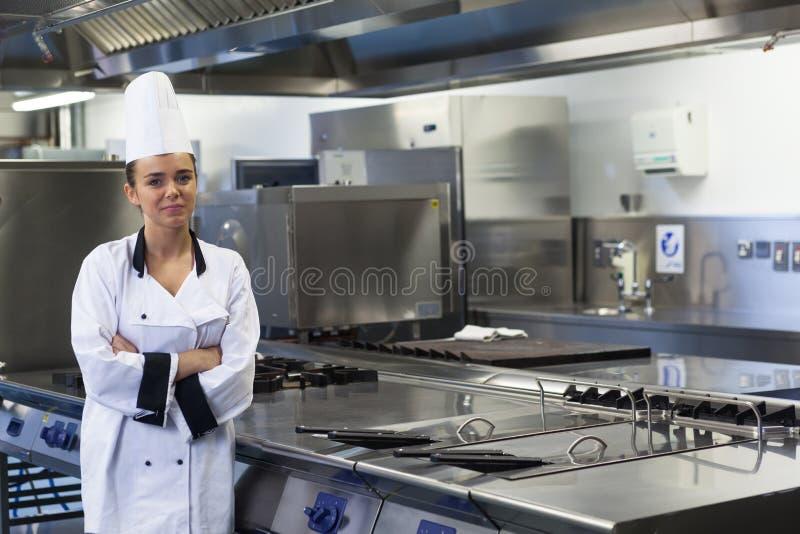 Młoda szczęśliwa szef kuchni pozycja obok pracy powierzchni ręk krzyżować fotografia stock