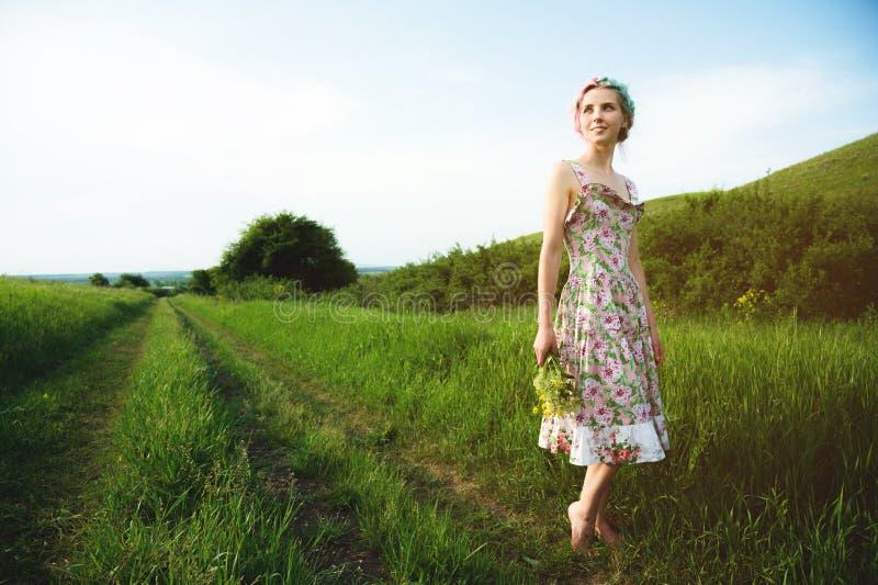 Młoda szczęśliwa uśmiechnięta dziewczyna w cycowej sukni z bukietem chodzi wzdłuż wiejskiej drogi z zieloną trawą obrazy royalty free