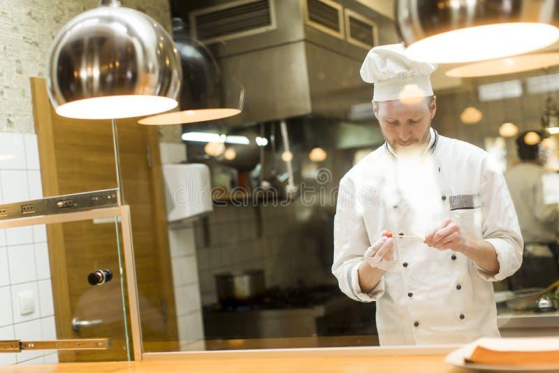Młoda szef kuchni pozycja w nowożytnej kuchni w pr i restauraci fotografia royalty free