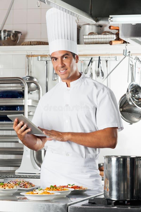 Młoda szefa kuchni mienia pastylka Z makaronów naczyniami Przy zdjęcie stock
