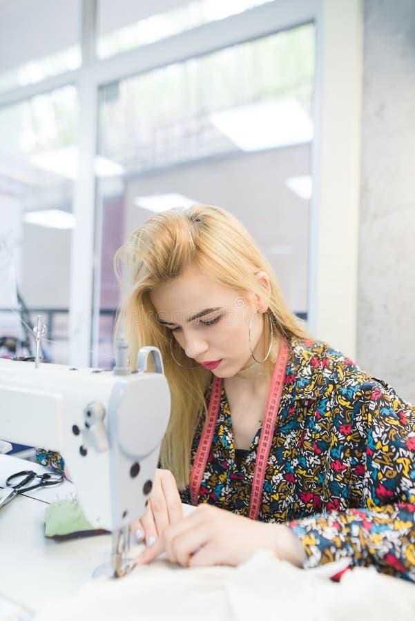 Młoda szwaczka pracuje na szwalnej maszynie w miejsce pracy obrazy stock