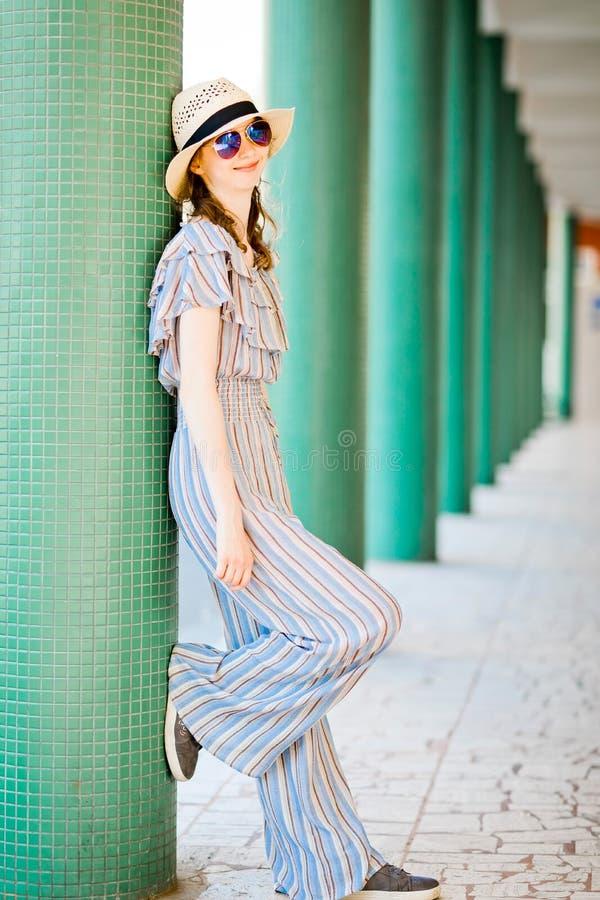 M?oda teenaged dziewczyna w kombinezonu smokingowy pozowa? przy kolumnad? zdjęcie royalty free