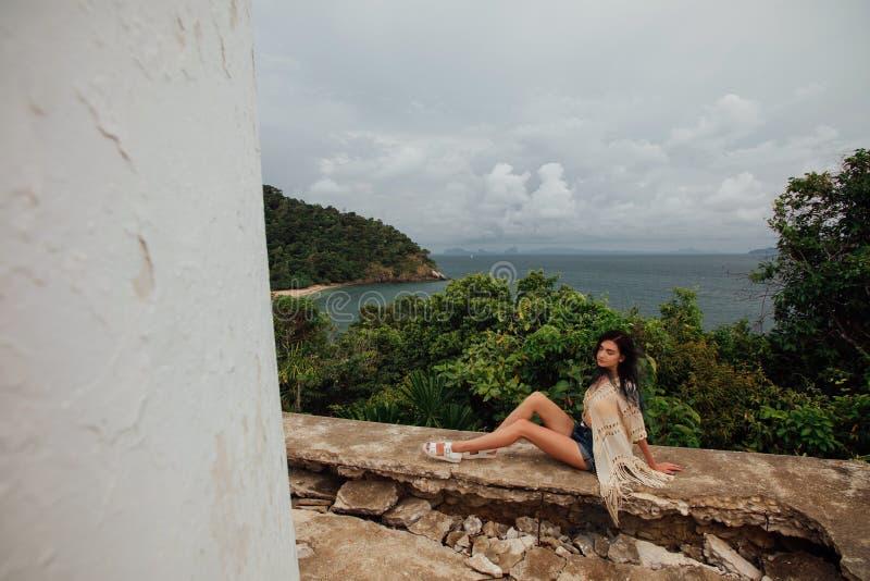 Młoda turystyczna dziewczyna siedzi na dachu rujnujący budynek przeciw tłu dennego brzeg zatoka obraz stock