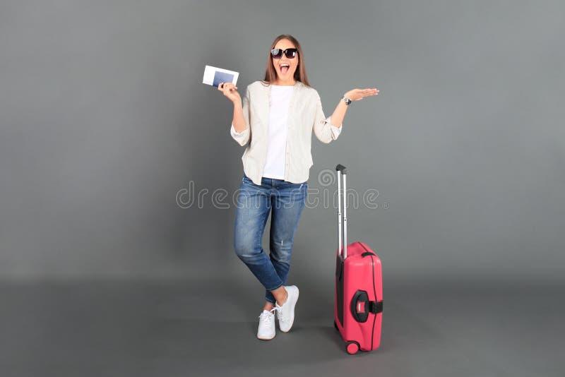 Młoda turystyczna dziewczyna w lat przypadkowych ubraniach z okularami przeciwsłonecznymi, czerwona walizka, paszport, bilety odi obraz royalty free