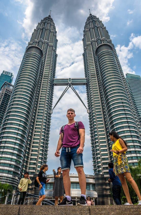 Młoda turystyczna pozycja pod Petronas Góruje w Kuala Lumpur, Malezja zdjęcie stock