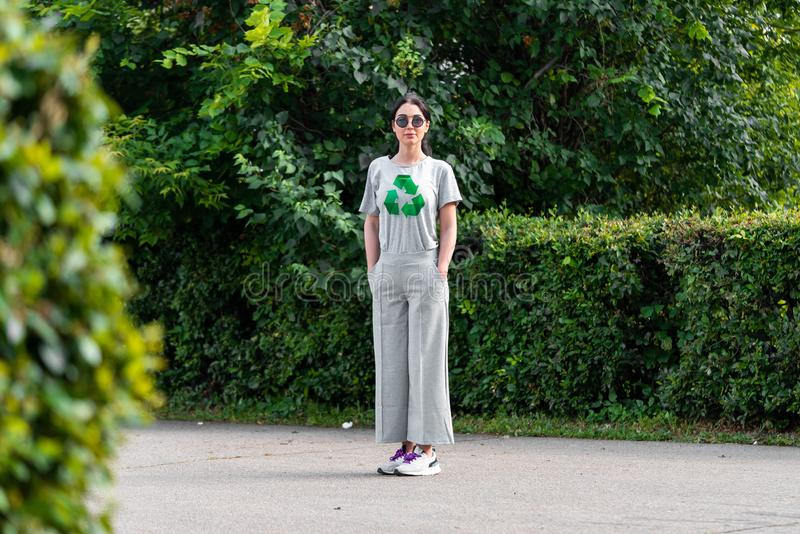 Młoda uśmiechnięta atrakcyjna kobieta w szarej koszulce z przetwarza symbol w parku zdjęcie stock